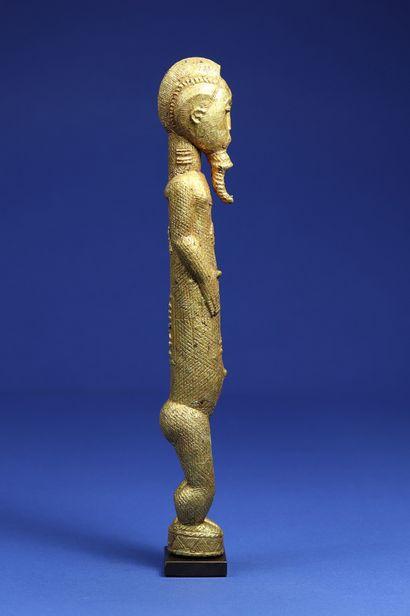 Elégante statuette représentant un personnage masculin debout, les bras courts serrés...