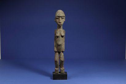 Statuette représentant un personnage féminin debout. Bois à patine croûteuse. Lobi,...