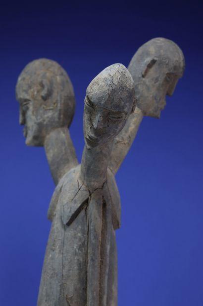 Rare et imposante statue figurant un corps tricéphale, les bras collés au buste...