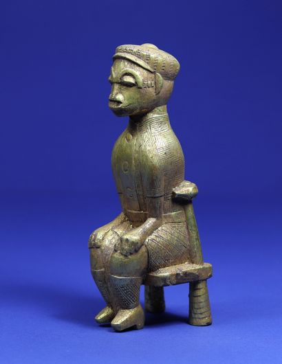 Statuette representing a character sitting on a chair, dressed in European style...