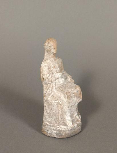 Figurine péplophore assise, tenant sur ses genoux un coffre ouvert.  Terre cuite...