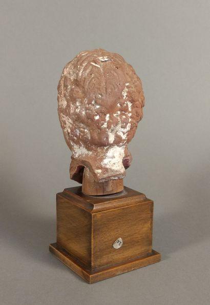 Tête ex-voto représentant un enfant dont la coiffure est tressée au milieu du crâne....