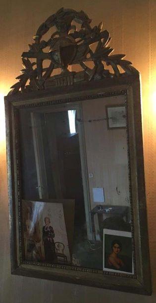 Miroir En bois sculpté et doré orné d une frise de perles, le fronton à décor ajouré...