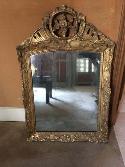 Miroir en bois sculpté et doré A décor de rinceaux, le fronton ajouré à décor de...