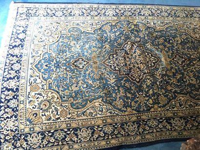 Grand tapis persan à fond bleu à décor de...