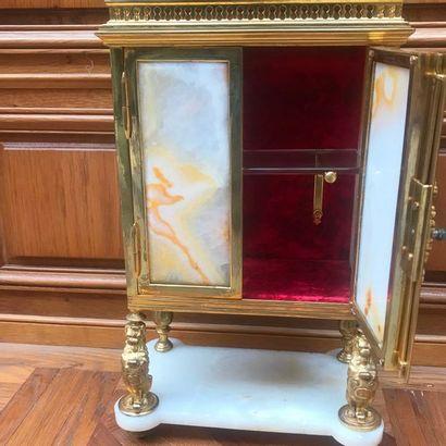 ARMOIRETTE en cabinet à panneaux d'albâtre dans une monture de laiton doré. Elle...
