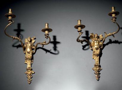 PAIRE D'APPLIQUES À DEUX LUMIÈRES en bronze doré et ciselé. Les fûts sous la forme...