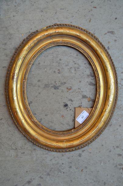 Cadre ovale en bois mouluré et stuc doré...