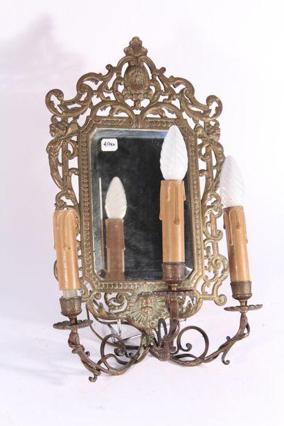 Applique à trois bras de lumière en bronze formant miroir à décor ajouré de rinceaux...