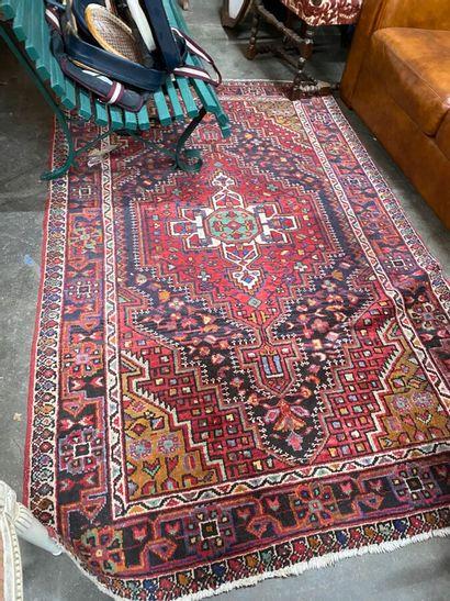 Tapis en laine points noués à décor géométrique sur fond rouge  Iran, Xxème sicèle...