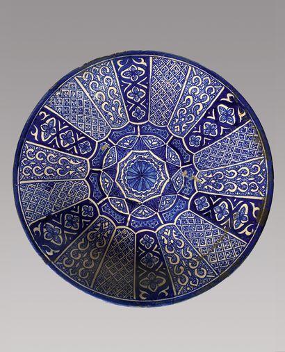 Grand plat en faïence à décor rayonnant bleu...
