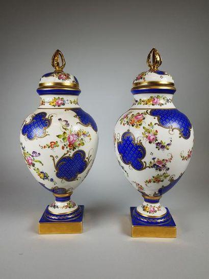 Paire de vases couverts (un couvercle restauré)...