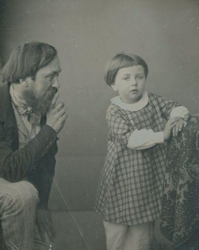Photographe non identifié Homme recommandant le calme à un garçonnet pour la pose...