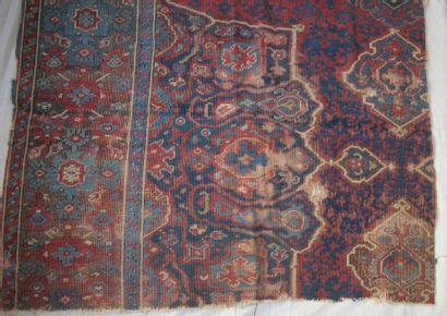 Fragment de tapis Ouchak, XVIIIème siècle, fond rouge, décor bleu de fleurs stylisées...