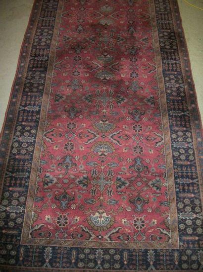 Tapis Mahal ( ?), fond rouge, décor en camaïeu bleu de fleurs, bordure bleue de...