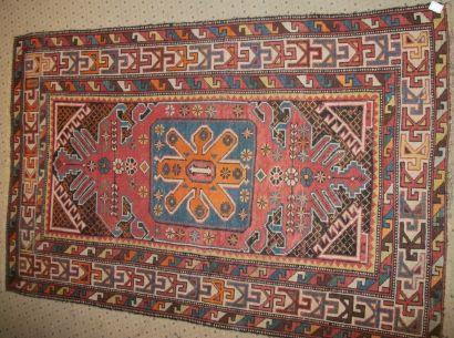 Tapis Lankora, XIXème siècle, fond rouge, décor d'un médaillon bleu chargé d'une...