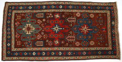 Tapis Kazak, XIXème siècle, fond prune, décor de trois médaillons vert, rouge et...