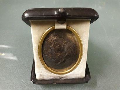 Médaillon en métal doré, contenant une mèche...