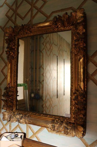 Glace en bois doré à décor de fleurs  Style...
