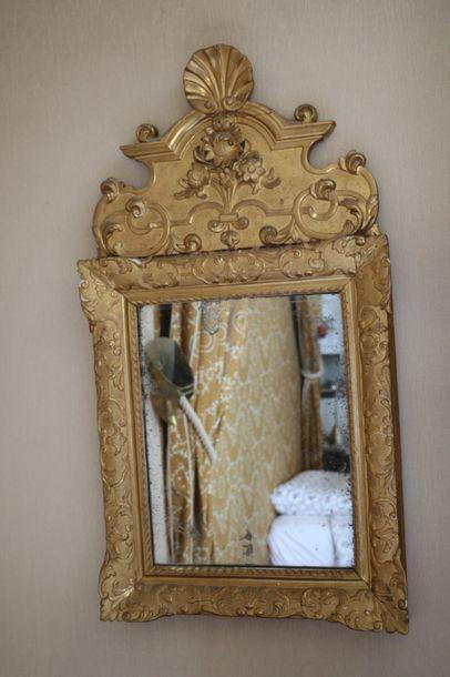 Glace en bois doré, à fronotn sculpté de...