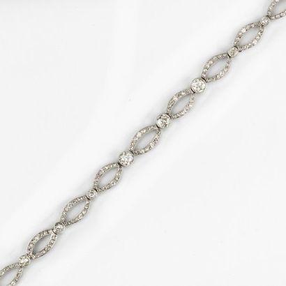 CARTIER. Bracelet ajouré en or gris (750 millièmes) serti de 9 diamants taille ancienne...