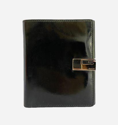 GUCCI. Portefeuille en cuir vernis noir....
