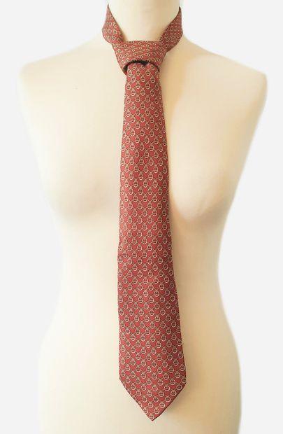 HERMES. Cravate en soie à fond couleur rouille...