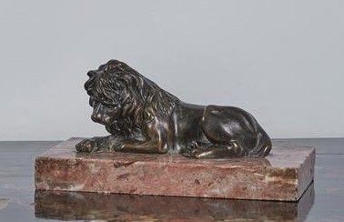 Lion couché en bronze patiné sur un socle...