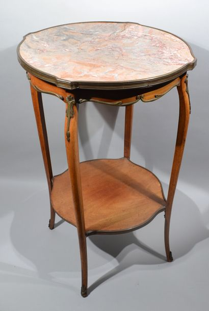 Veneer siding table with a round, pink marble scrolled top surrounded by a brass...