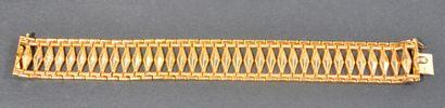 BRACELET ARTICULÉ en or jaune 18K (750/1000e) à décor d'une frise de losanges ajourés....