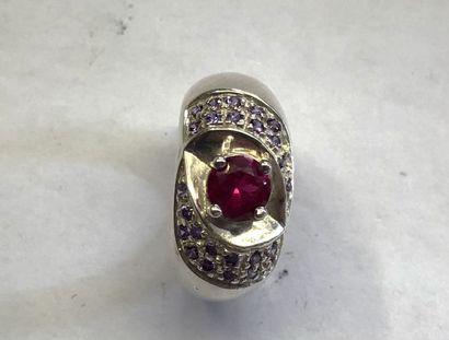 BAGUE en argent 925/1000e sertie d'une pierre rouge rose flanquée de pierres violettes....
