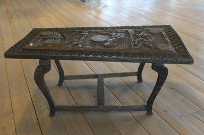 Table basse africaine à décor de scènes villageoises, XXe, bois sculpté et patiné,...