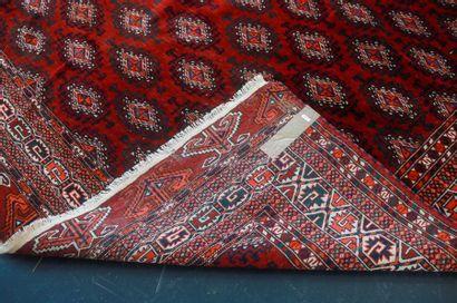 Grand tapis turkmène à semis de göls sur champ rouge foncé, 325x214 cm env.