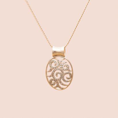 Pendentif ovale en or jaune 375°/00 ajouré de motifs de méandres sertis de diamants...