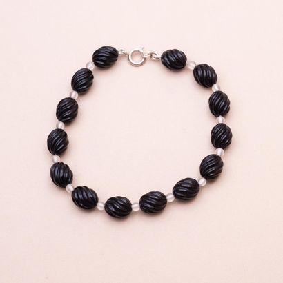 Bracelet en argent sup. 800°/00 composé de perles ovales d'onyx rainuré alternées...