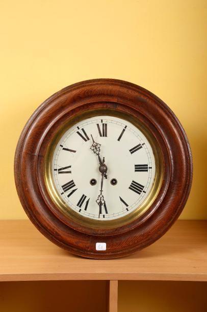 Une horloge murale ronde en chêne.