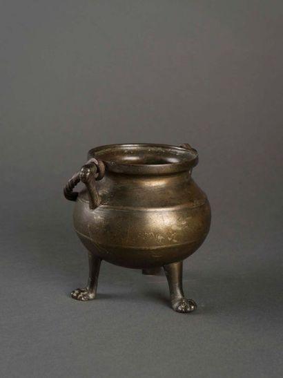 Marmite tripode en bronze patiné, anses soulignées...