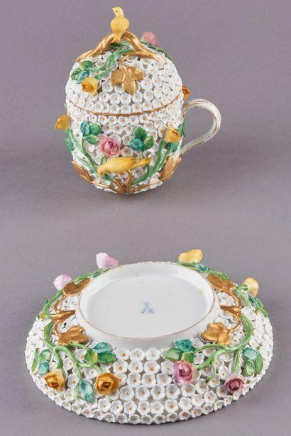 MEISSEN. Tasse couverte et sa sous-tasse en porcelaine à décor en relief de coroles...