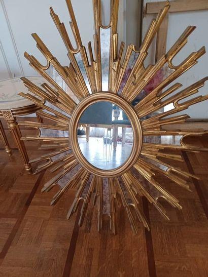 Grand miroir rayonnant en bois doré, dans...
