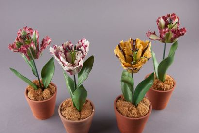 Quatre tulipes en porcelaine, les tiges en tôle laquée vert. Dans des pots en terre...