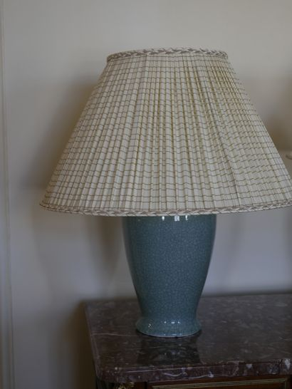 A celadon porcelain lamp base with cracks. A patinated bronze lamp base with three...