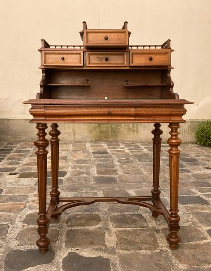Bonheur du jour in molded and carved natural wood opening with a drawer in the waist...