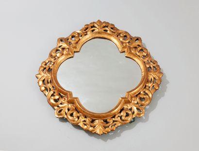 Miroir en bois sculpté et doré de forme chantournée à décor de volutes et de rinceaux...