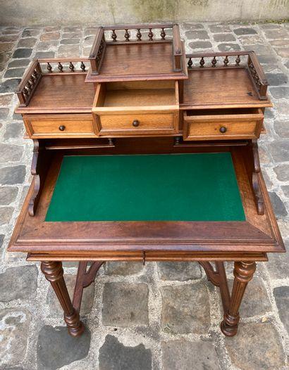 Bonheur du jour en bois naturel mouluré et sculpté ouvrant par un tiroir en ceinture...