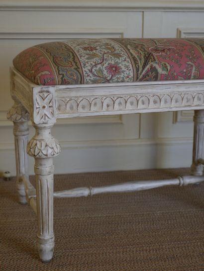 Banc en bois mouluré sculpté laqué crème, pose sur six pieds fuselés cannelés réunis...