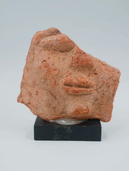 Fragment de visage de couvercle votif. Terre...
