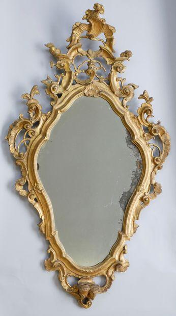 Miroir en bois sculpté doré à décor de volutes.Italie...