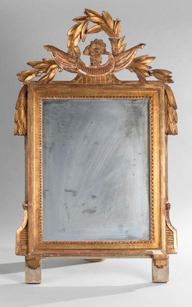 Miroir en bois doré mouluté et sculpté à...