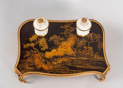 Ecritoire de bureau, le plateau en laque noir et or à décor d'un paysage animé de...