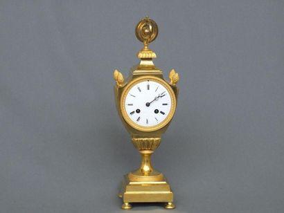Pendule en forme d'urne en bronze doré ,...